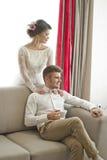 在爱的婚礼夫妇 白色礼服的美丽的新娘有英俊的新郎的 明亮的内部 免版税图库摄影