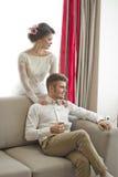 在爱的婚礼夫妇 白色礼服的美丽的新娘有英俊的新郎的 明亮的内部 库存照片