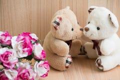 在爱的容忍熊在花束附近坐上升了 图库摄影