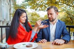 在爱的年轻夫妇在咖啡馆坐,并且妇女哺养结块她的人 库存图片