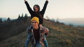 在爱的年轻夫妇在度假享用山的 可爱的人运载他的肩膀和旋转的女朋友 股票视频