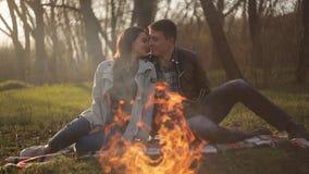 在爱的年轻夫妇在火的一个日期 人和女孩敬佩火的火焰 影视素材