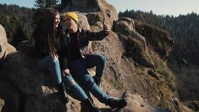 在爱的年轻夫妇坐岩石和与朋友的制造视频聊天 旅游业,通信,休息,聊天的概念 影视素材