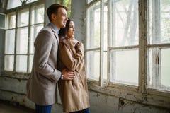 在爱的年轻夫妇拥抱并且看窗口 里面 免版税库存图片
