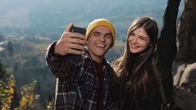 在爱的年轻夫妇站立高在山的一个岩石和与朋友的制造视频聊天 旅游业,通信 股票录像