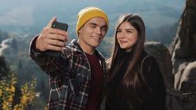 在爱的年轻夫妇站立高在山的一个岩石和与朋友的制造视频聊天 旅游业,通信 股票视频
