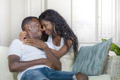 在爱的年轻美好和愉快的黑非裔美国人的夫妇放松在现代家庭在沙发长沙发的客厅拥抱的甜点 免版税库存照片