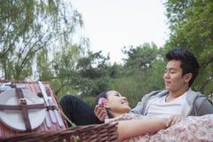在爱的微笑的夫妇有野餐在公园,躺下在有开放野餐的篮子的毯子 免版税库存图片