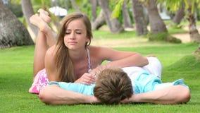在爱的微笑的夫妇,谈话和拥抱在棕榈树下 股票录像