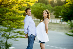 在爱的愉快的夫妇一起在日落的公园风景与妇女怀孕的腹部和人 库存照片