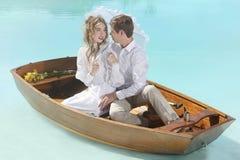 在爱的愉快的夫妇在一条小船户外 免版税库存照片