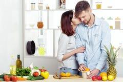 在爱的愉快的夫妇在做健康汁液的厨房里由新鲜的桔子 夫妇亲吻 免版税库存照片