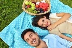 在爱的愉快的夫妇在浪漫野餐在公园 关系 库存照片