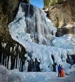 在爱的愉快的夫妇在瀑布附近 免版税库存照片