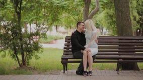 在爱的愉快的夫妇坐一条长凳在城市公园 股票视频