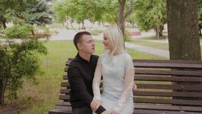 在爱的愉快的夫妇坐一条长凳在城市公园 股票录像