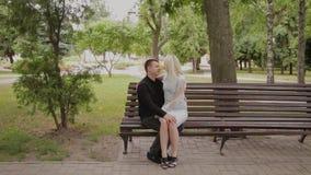 在爱的愉快的夫妇坐一条长凳在城市公园 影视素材