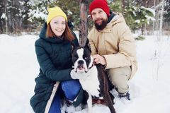 在爱的愉快的夫妇获得乐趣在与他的小狗的雪 免版税图库摄影