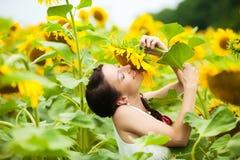 在爱的愉快的夫妇获得乐趣在领域充分的向日葵 库存照片