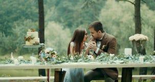 在爱的愉快的夫妇谈和轻轻地握手,当坐在桌上deocrated与叶子,花和时 股票视频