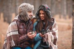 在爱的愉快的夫妇,报道用毯子,坐在秋天森林里和饮用的热的茶 免版税图库摄影