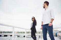 在爱的愉快的年轻夫妇在一件美丽的礼服,摆在码头在水附近 免版税图库摄影