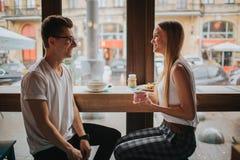 在爱的愉快的年轻夫妇有一个好日期在酒吧或餐馆 他们讲关于他们自己的有些故事 库存图片
