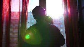 在爱的愉快的年轻夫妇来到窗口 人轻轻地拥抱女孩并且亲吻她 通过太阳` s光芒通行证 股票视频
