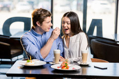在爱的愉快的年轻夫妇在浪漫日期在餐馆 免版税库存照片
