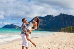 在爱的愉快的年轻夫妇在海滩海 免版税库存照片