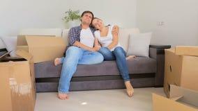 在爱的愉快的年轻夫妇坐沙发和高兴他们新的公寓 股票视频