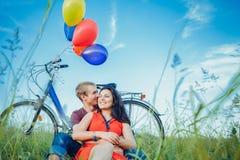 在爱的愉快的年轻成人夫妇在领域 两,男人和妇女有野餐,微笑和基于绿草 免版税库存图片