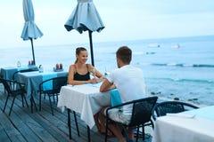 在爱的浪漫夫妇吃晚餐在海海滩餐馆 库存图片