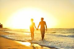 在爱的浪漫蜜月夫妇在海滩日落 免版税库存图片