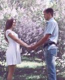 在爱的甜年轻夫妇反对开花的春天 库存照片