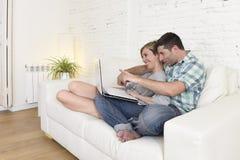 在爱的美好的夫妇在与便携式计算机一起的长沙发愉快在家使用互联网 库存照片