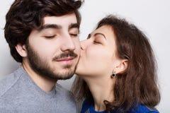 在爱的美好的夫妇在白色背景 热情地亲吻他下巴的女朋友时髦的男朋友 一bearde 图库摄影
