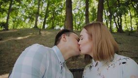 在爱的美好的愉快的夫妇坐一条长凳在公园和亲吻 影视素材