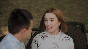 在爱的美好的愉快的夫妇坐一条长凳在公园和谈 股票录像