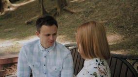 在爱的美好的愉快的夫妇坐一条长凳在公园和谈 影视素材