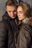 在爱的美好的愉快的逗人喜爱的夫妇拥抱,并且眼睛闭上在日落在墙壁附近在一个温暖的晚上落 图库摄影