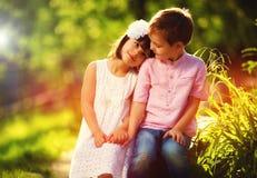 在爱的逗人喜爱的孩子,一起坐在春天庭院里 免版税库存图片