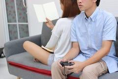 在爱的逗人喜爱的年轻亚洲夫妇和有幸福在客厅 免版税库存图片
