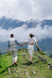 在爱的,握手和享受在山的一对年轻夫妇的背面图美好的风景 库存图片