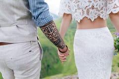 在爱的,握手和享受在山的一对年轻夫妇的背面图美好的风景 图库摄影