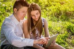 在爱的年轻夫妇使用一种片剂在庭院里 图库摄影