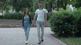 在爱的年轻夫妇在公园和举行手上走