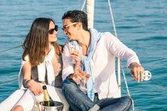 在爱的年轻夫妇在有香槟槽的帆船 免版税库存照片