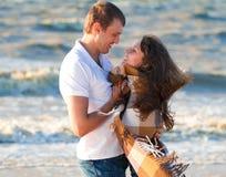 在爱的年轻夫妇在毯子包裹的海滩 库存图片