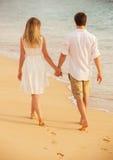 在爱的年轻夫妇在海滩日落 免版税图库摄影